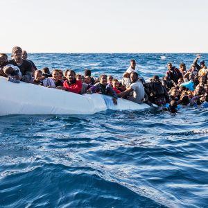 Siirtolaisia kumiveneessä meressä.