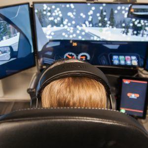 Nuori ajaa ajosimulaattorilla.