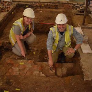 Kaksi hymyilevää arkeologia suojaliiveissä ja kypärissä kaivamassa kivirakennelmaa talon lattian alta.
