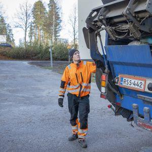 Jäteauton kuljettaja Elias Sibakov tyhjentää jäteastioita autoon.