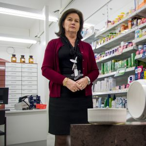 Kaukovainion sivuapteekin omistaja Aila Aitamurto seisoo apteekissaan. Etualalla avattu lääkepurkki.