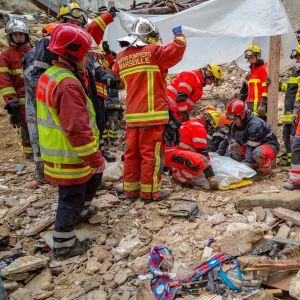 romahtanut kerrostalo ja pelastajia