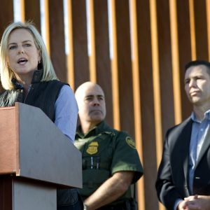 Vaalea hiuksinen nainen puhujan pöntössä, taustalla seisoo kaksi miestiä ja punaruskeaa aitaa.