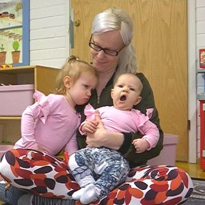 Äiti ja kaksi lasta istuvat seurakunnan perhekerhon lattialla