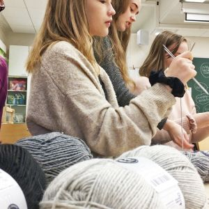 Yhdeksännen luokan tytöt neulomassa sukkia.