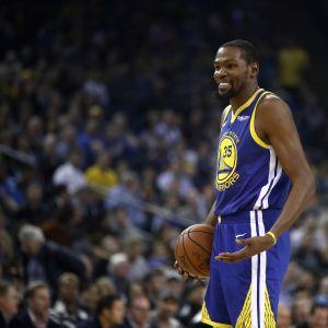 Kevin Durant hymyilee kentällä.