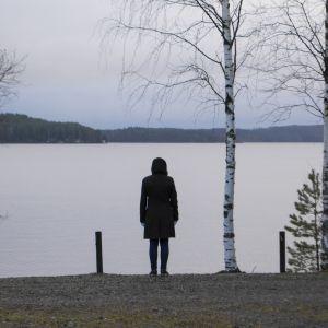 Naisen siluetti järveä vasten.