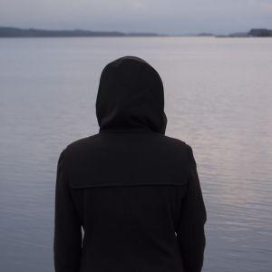 Ihmisen siluetti järveä vasten.