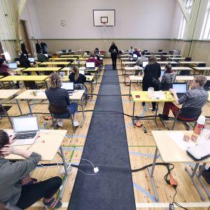 Kokelaat valmistautuvat tekemään sähköisen ylioppilaskirjoituksen Ressun lukiossa Helsingissä.