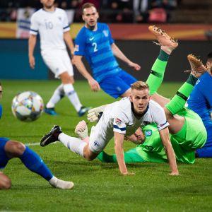 Suomen Jasse Tuominen kamppailee pallosta Kreikan pelaajia vastaan.