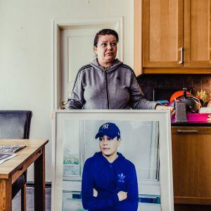 nainen ja kehystetty kuva pojastaan