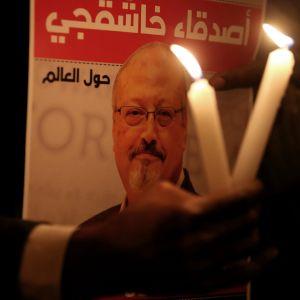 Mielenosoittaja kantaa Jamal Khashoggin kuvaa ja kahta palavaa kynttilää Saudi-Arabian konsulaatin edessä Istanbulissa, Turkissa.