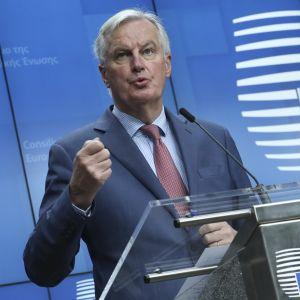 Kuvassa Michel Barnier puhujanpöntön takana. Taustalla EU:n symboli.
