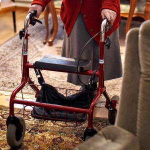 Vanhus liikkuu rollaattorin avulla kotonaan.