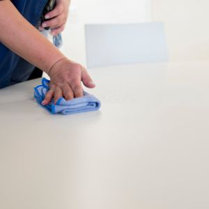 Nainen pyyhkii pöydän pintaa liinalla.
