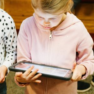 Kaksi tyttöä lukemassa tablettikoneiltaan.