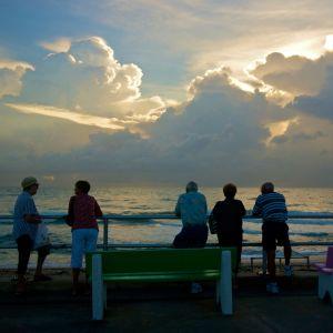 Ihmiset katsovat auringonlaskua.