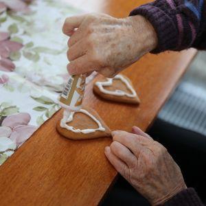 Vanhus koristelee pipareita.