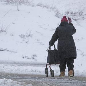Vanhempi nainen kävelee rollaattoriin tukeutuen talvista tietä.