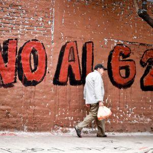 Mies kulkee kadulla, seinään on kirjoitettu vastalause G20- kokousta vastaan.