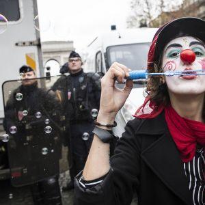 Mielenosoittaja pukeutunut kolvniksi ja puhaltelee saippuakuplia.