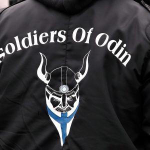 Soldiers of Odinin logo takin selässä.