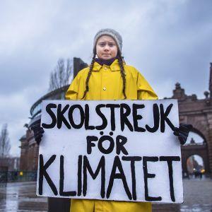 """15-vuotias ruotsalainen Greta Thunberg pitelee kylttiä, jossa lukee """"koululakko ilmaston puolesta"""". Hän istuu Ruotsin parlamenttitalon edessä perjantaisin, kunnes maa noudattaa Pariisin sopimuksen mukaista ilmastopolitiikkaa."""