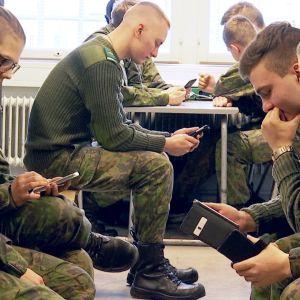 varusmiehiä käyttämässä älypuhelimia