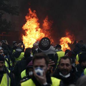 Keltaliivisiä mielenosoittajia, joiden takana palaa katollaan oleva auto