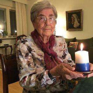 Brita Oranen sytyttää itsenäisyyspäivän kynttilän kodissaan Mikkelin keskussa.