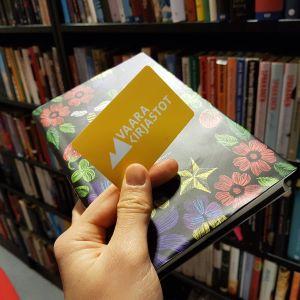 Kädessä kirja ja Vaara-kirjaston kirjastokortti, taustalla kirjahylly.