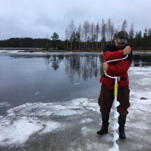 Etelä-Pohjanmaan kalatalouskeskuksen toiminnanjohtaja Marko Paloniemi kairaamassa jäähän reikää