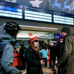 Ihmiset yrittävät saada tietoa junien aikatauluista Kölnin rautatieasemalla.