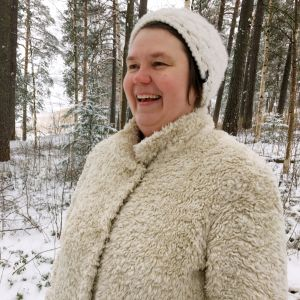 Reetta Tourunen hymyilee metsässä.