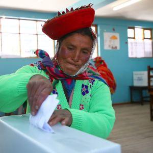 Nainen pudottaa äänestyslipun vaaliuurnaan äänestyspaikalla Cuscossa, Perussa.