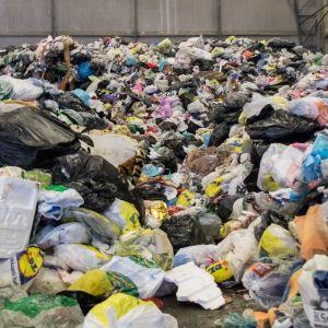 Kotitalousjätettä Kukkuroinmäen jätekeskuksessa. Jätteet säilötään hallissa väliaikaisesti ja viedään Riihimäelle poltettavaksi.