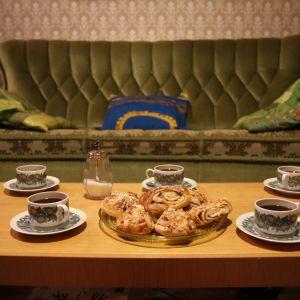 Kahvikuppeja pöydällä, sohva taustalla