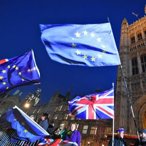 Iso-Britannian ja EU:n liput liehuvat Lontoon parlamenttirakennuksen edustalla. Muutamia mielenosoittajia on paikalla.