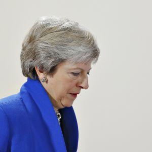 Theresa May kuvattuna vaaleanharmaata taustaa vasten.