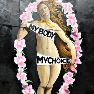 """Nainen katselee seinälle maalattua muraalia, jossa alaston nainen kannattelee tekstiä: """"Minun kehoni. Minun valintani"""". Alaston nainen on toisinto italilaisen kuvataiteilijan Sandro Botticellin Venus-hahmosta. Naisen ympärillä kiertää kukkaseppele."""