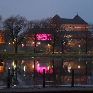 Hämeen linnan yksi seinistä valaistu purppuran värillä