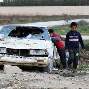 Lapset leikkivät autonromussa