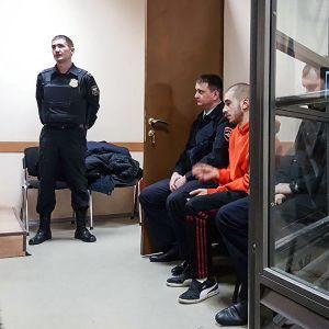 Venäläinen rap-artisti Husky odottaa poliisien kanssa pääsyä oikeussaliin.