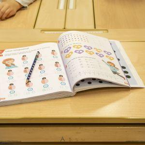 Pöydällä kirja ja pienen koululaisen kädet.