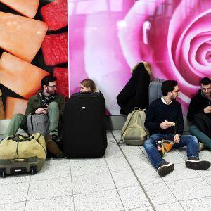 Matkustajia odottamassa lentotietoja Gatwickin lentokentällä perjantaina.
