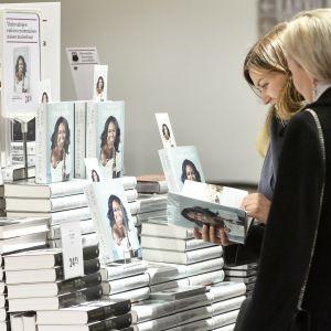 Naiset selailevat Michelle Obaman kirjaa Suomalaisessa Kirjakaupassa