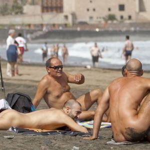 Kolme alastonta miestä lekottelee rannalla.