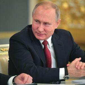 Venäjän presidentti Vladimir Putin istuu pöydän ääressä ja katsoo vierelleen.