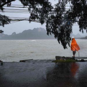 Sadeviittaan pukeutunut mies kävelee tuulisella rannalla tänään eteläisessä Surat Thanin maakunnassa Thaimaassa.