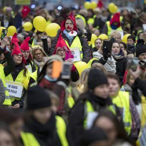 Naiset marssivat keltaisiin liiveihin pukeutuneina sunnuntaina Pariisissa.